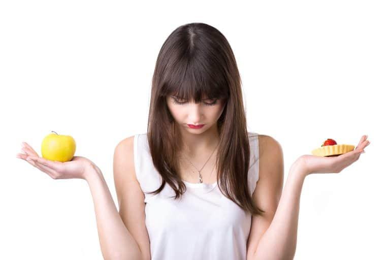 Uma mulher com a cabeça baixa e semblante triste segurando uma fruta em uma mão e uma torta de morango na outra. Provavelmente em dúvida do que comer, por medo de comer o doce por conta dos riscos da diabetes.