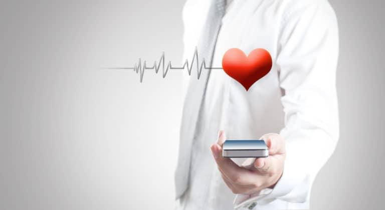 Imagem de um médico segurando um celular utilizando um aplicativo médico.