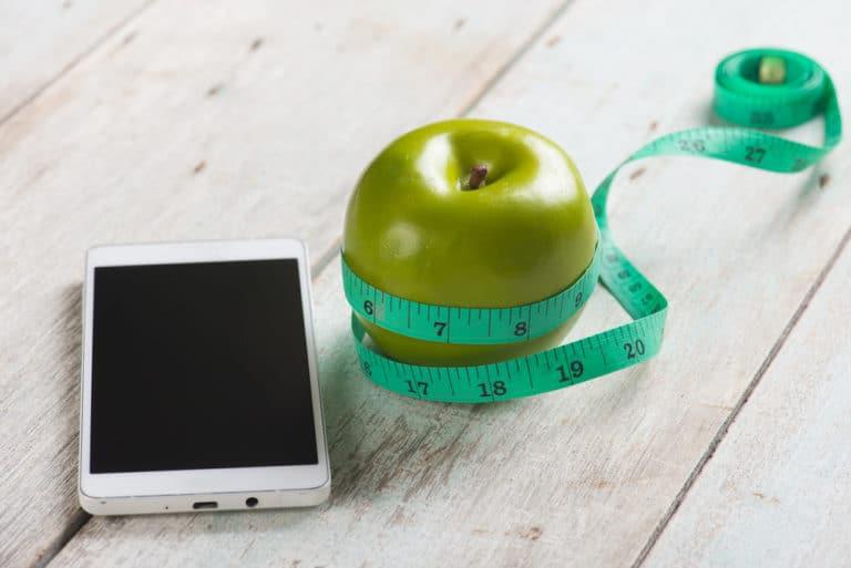 Um celular ao lado de uma maçã verde enrolada em uma fita métrica, fazendo alusão aos aplicativos de saúde que podem nos ajudar diariamente.