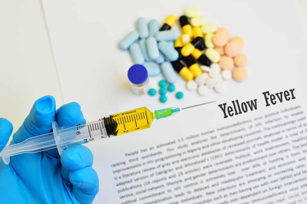 imagem de uma mão com luva segurando uma seringa com remédio para febre amarela